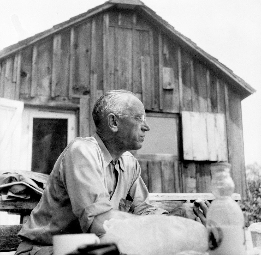 Aldo Leopold seated with shack in background, circa. 1940. ------ MANDATORY CREDIT: Courtesy of the Aldo Leopold Foundation, www.aldoleopold.org